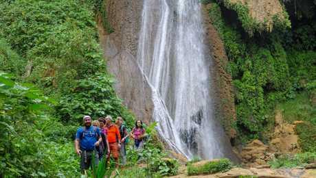 Randonneurs devant une cascade à Topes de Collantes