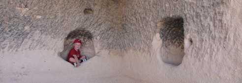 Enfant assis dans la cavité d'une maison troglodyte en Cappadoce