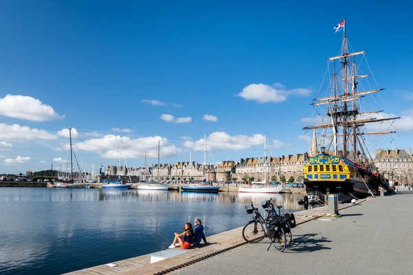 Cyclistes sur le port de Saint Malo avec le bateau l'étoile du roy en fond
