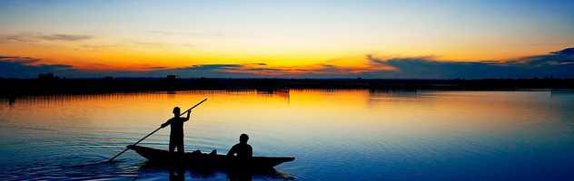 Bateau sur la lagune de Tam Giang au coucher de soleil
