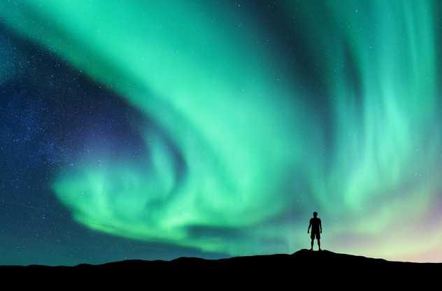 Homme admirant une aurore boréale