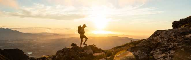 Randonneur au coucher de soleil dans les Alpes