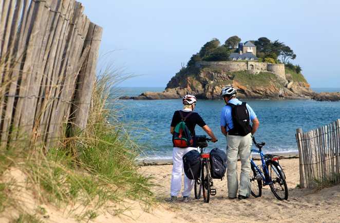 Cyclistes face à la mer sur la côte d'Emeraude en Bretagne