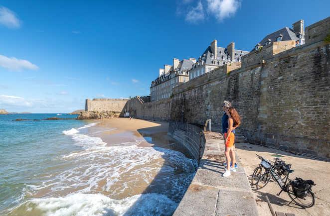 Cyclistes sur la plage de Saint-Malo avec les remparts et la ville intra-muros en fond