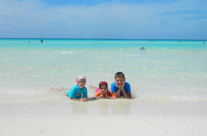 Enfants en bord de plage, allongés dans l'eau à Cayo Santa Maria à Cuba