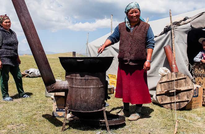 Femme kirghize préparant le repas devant la yourte en Kirghizie