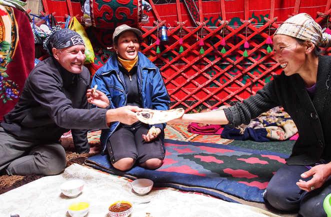 Partage du repas entre les voyageurs et les habitants dans une yourte en Kirghisie